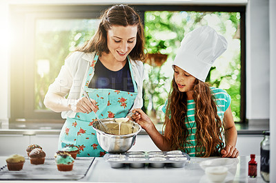 Buy stock photo Shot of a mother and her daughter baking in the kitchen