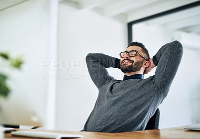 Buy stock photo Shot of a young designer taking a break at his office desk