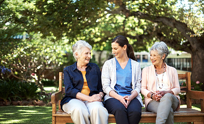 Buy stock photo Shot of two senior women and a nurse sitting together on a bench out in the garden