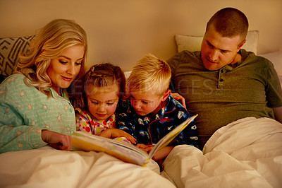 Buy stock photo Cropped shot of a family reading a bedtime story together at home