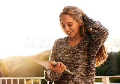 Buy stock photo Cropped shot of an attractive young woman using a digital tablet outside