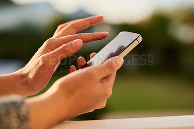 Buy stock photo Closeup shot of an unrecognisable woman using a cellphone outside