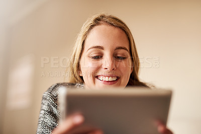Buy stock photo Cropped shot of an attractive young woman using a digital tablet at home