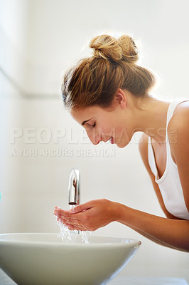 Buy stock photo Shot of a beautiful young woman washing her face in the bathroom at home