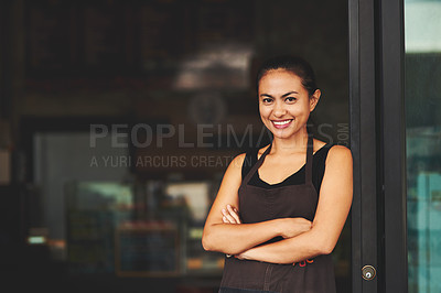 Buy stock photo Portrait of a young barista posing with her arms crossed in a coffee shot