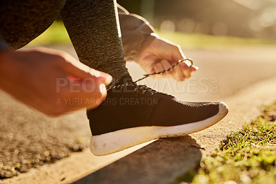 Buy stock photo Shot of an unidentifiable young woman tying her shoelace before going on a run