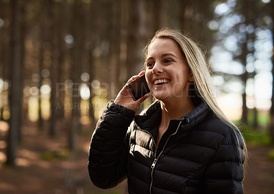 Buy stock photo Shot of a happy young woman talking on her cellphone while walking in the forest