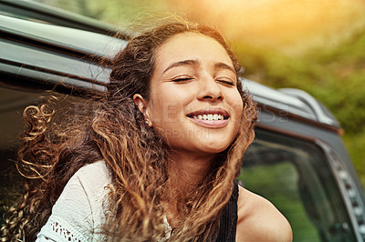 Buy stock photo Cropped shot of a young woman leaning out the window of a car while on a roadtrip