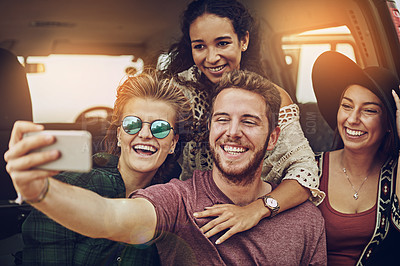 Buy stock photo Cropped shot of a group of friends taking a selfie while on a roadtrip together