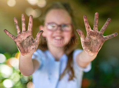 Buy stock photo Portrait of a little girl showing her muddy hands outside