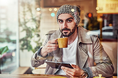 Buy stock photo Portrait of handsome young man drinking a coffee and using a digital tablet while sitting at a counter in a cafe