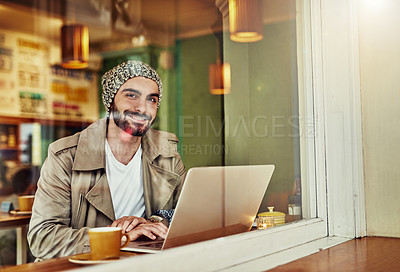 Buy stock photo Portrait of a stylish young man smiling while drinking a coffee and using a laptop in a cafe