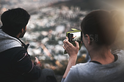 Buy stock photo Rearview shot of a young couple taking photographs of the view while mountain hiking