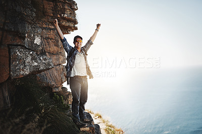 Buy stock photo Portrait of a young man standing on a mountain cliff with his arms raised