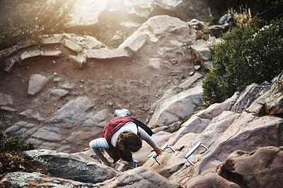 Buy stock photo Shot of a young woman climbing a ladder while hiking in the mountains