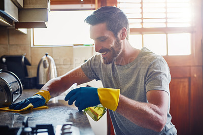 Buy stock photo Cropped shot of a young man cleaning a kitchen surface at home