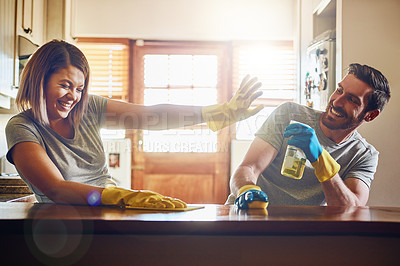Buy stock photo Cropped shot of a young couple having fun while doing chores together at home