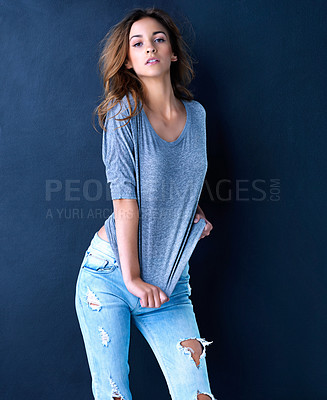 Buy stock photo Studio portrait of a cute teenage girl pulling on her shirt posing against a dark background