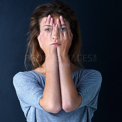 Buy stock photo Studio shot of a teenage girl with her face superimposed on hands covering her eyes against a dark background