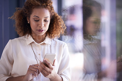 Buy stock photo Shot of a young businesswoman using a smartphone at work