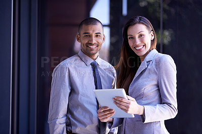 Buy stock photo Portrait of two colleagues using a digital tablet together at work