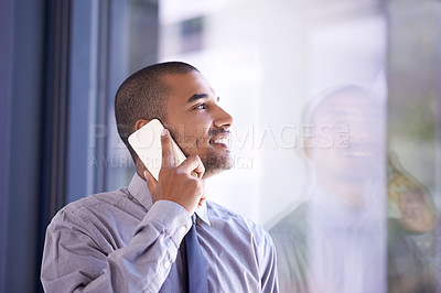 Buy stock photo Shot of a young businessman using his mobile phone to make a call at work