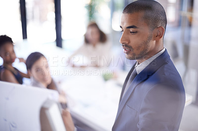 Buy stock photo Cropped shot of a businessman giving a presentation to his colleagues in the boardroom