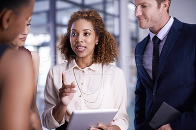 Buy stock photo Cropped shot of a group of businesspeople working together on a digital tablet in an office