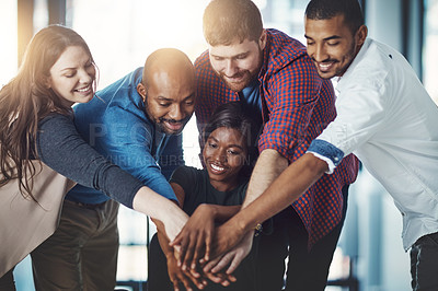 Buy stock photo Shot of a young work group joining hands in solidarity