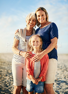 Buy stock photo Portrait of a little girl posing with her mother and grandmother on the beach
