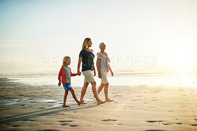 Buy stock photo Shot of a little girl walking on the beach with her mother and grandmother
