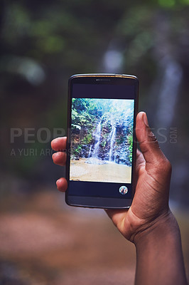Buy stock photo Shot of an unidentifiable young tourist taking a picture of a waterfall with his smartphone