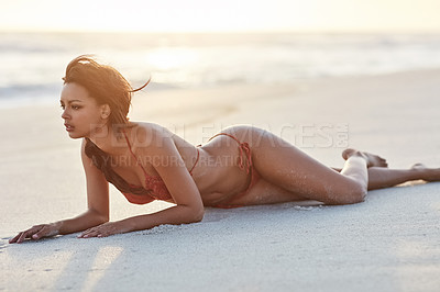 Buy stock photo Shot of a beautiful young woman lying on the beach