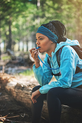 Buy stock photo Cropped shot of an athletic young woman taking a drink while jogging in the woods