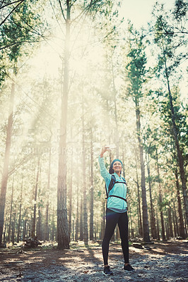 Buy stock photo Full length shot of an athletic young woman taking selfies while jogging in the woods