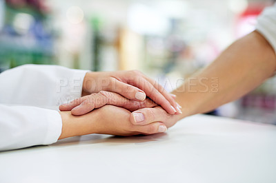 Buy stock photo Cropped shot of a pharmacist  compassionately holding a customer's hand
