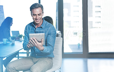 Buy stock photo Shot of a businessman using a digital tablet with his colleagues blurred in the background