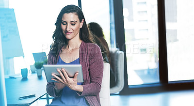 Buy stock photo Shot of a businesswoman using a digital tablet while sitting in an office