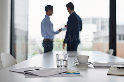 Buy stock photo Shot of paperwork on a table in an office with two businessmen having a discussion in the background