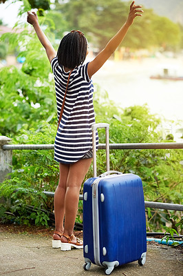 Buy stock photo Shot of a young woman standing with her arms in the air next to her suitcase outside in Thailand