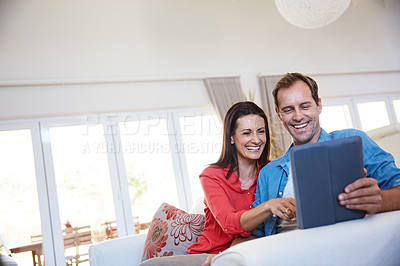 Buy stock photo Shot of a mature couple using a digital tablet together at home