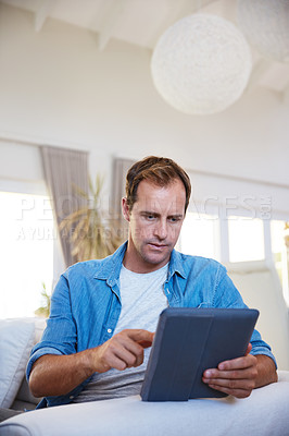 Buy stock photo Shot of a man using a digital tablet and relaxing on the sofa at home