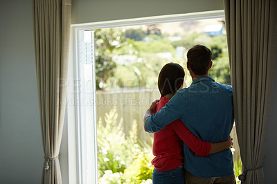 Buy stock photo Rear view shot of a mature couple looking out the window at home together