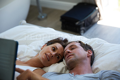 Buy stock photo Shot of a mature couple using a digital tablet while relaxing in bed together