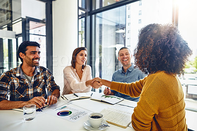 Buy stock photo Cropped shot of two designers shaking hands during a meeting in an office