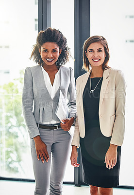 Buy stock photo Portrait of two confident young businesswomen standing together in an office