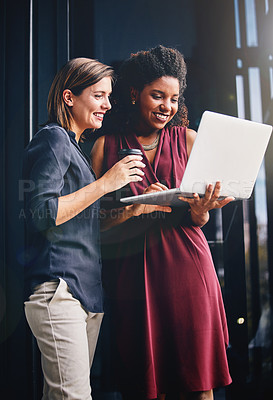 Buy stock photo Cropped shot of two young businesswomen using a laptop outside an office
