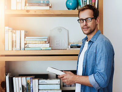 Buy stock photo Cropped portrait of a handsome man getting a book from his bookshelf