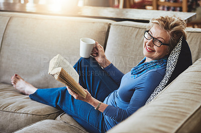 Buy stock photo Portrait of a senior woman relaxing with a warm beverage and a book on the sofa at home
