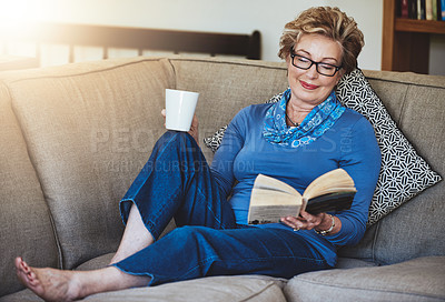 Buy stock photo Shot of a senior woman relaxing with a warm beverage and a book on the sofa at home